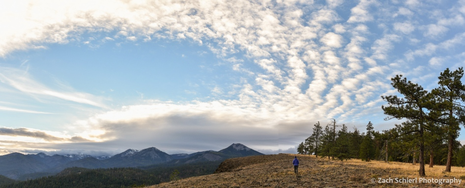 A hiker walks along a grassy meadow as clouds fill the sky overhead