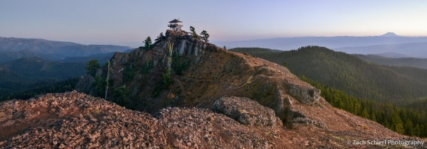 A rocky ridge with a lookout tower on top is seen as the sky darkens to twilight in the background