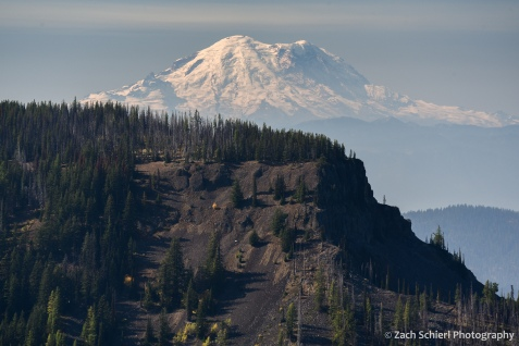 A tall snowy peak rises above dark volcanic cliffs in the foreground