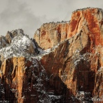 Cliffs of white and tan rock are streaked by dark red coloring, and dusted by a light layer of white snow.