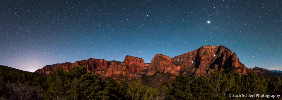 Stars and planets dot the sky over cliffs and canyons of red rock
