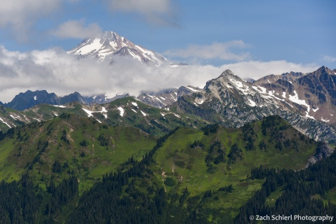 A tall mountain peak is just visible above clouds, with green meadows and forests belows.