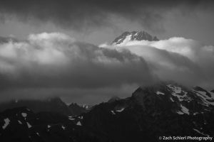 The summit of a glacier clad peak is visible through a break in the clouds