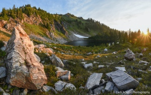 Sunrise light illuminates rocks in an alpine lake basin.