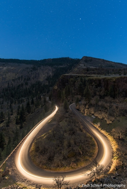 A streak of headlights illuminates a winding mountain road with stars overhead.