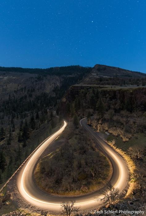 A streak of headlights illuminates a winding mountain road with stars overhead.