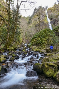 A waterfall and cascade flows through a verdant forest as a hiker looks on.