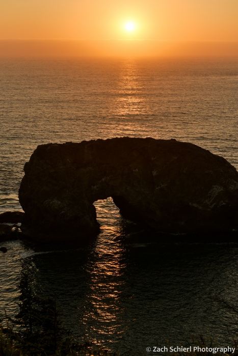 A large rock protruding from the ocean has an archway in it and the sunlight is passing through the archway, forming a narrow beam of sunlight on the ocean surface.
