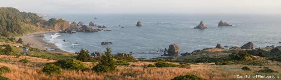 A panoramic view of a grassy slope, a sandy beach, blue ocean, and several rocky islands