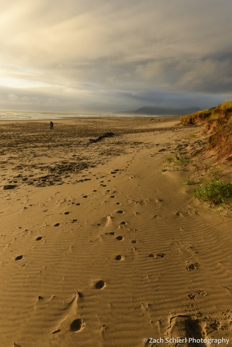 A sandy beach covered in footprints extends toward a horizon filled with dark clouds