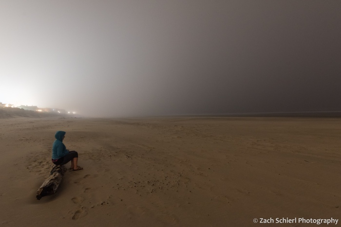 A person sits on a log on a sandy beach. Lights of a city are seen in the background reflecting off a thick layer of fog.
