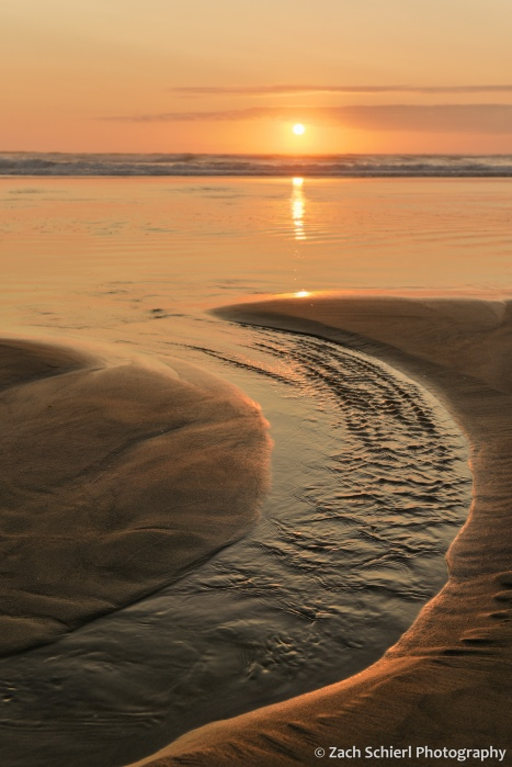 A rivulet of water enters the ocean while the sky overhead is bright orange at sunset.