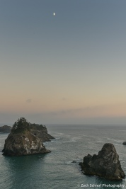 The first quarter moon hovers over sea stacks along the Oregon Coast south of Gold Beach,