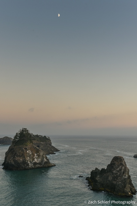 Several large rocky islands protrude from the ocean. The sky is dark blue and the first quarter moon hovers above them.