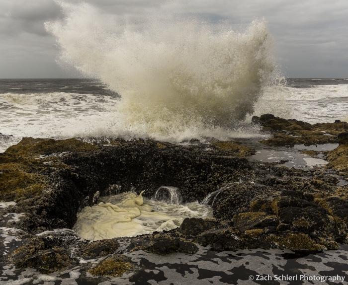 Large waves crash up against a coastline made of dark colored rock